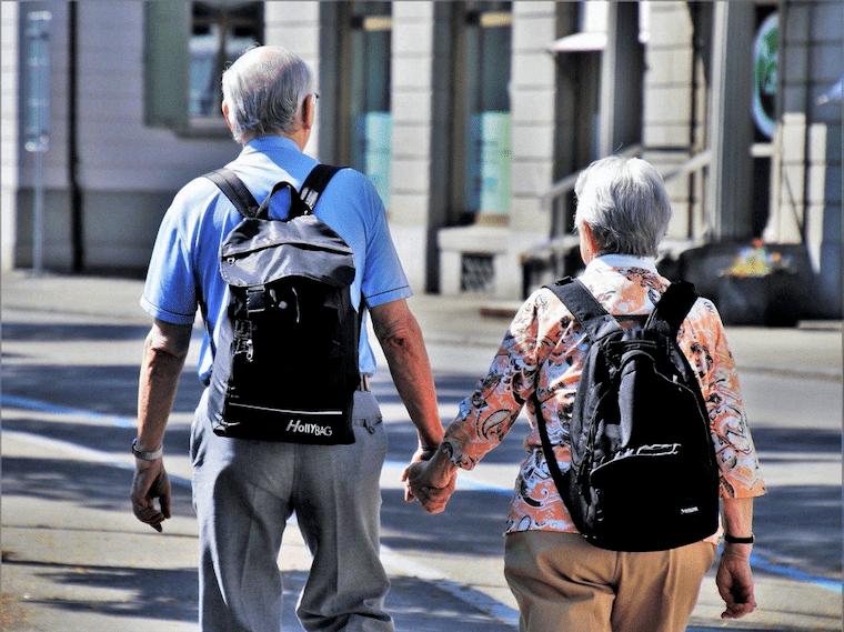 街を手をつないで歩く高齢者夫婦