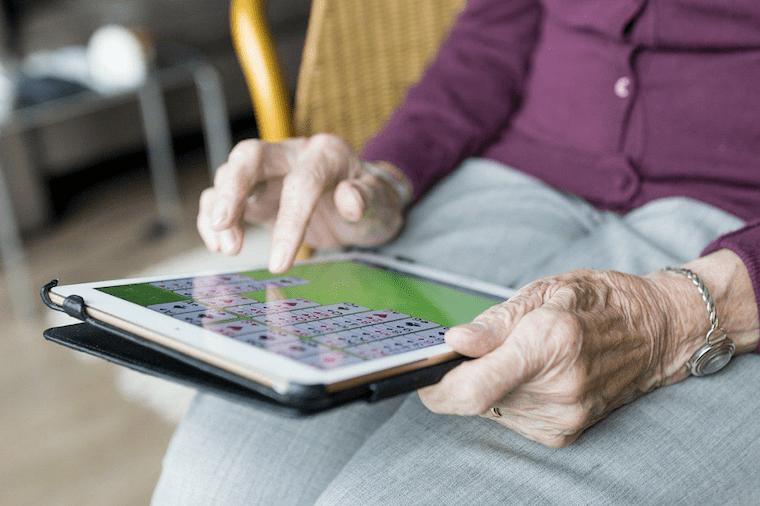 iPadでゲームをする高齢者女性の手元の様子